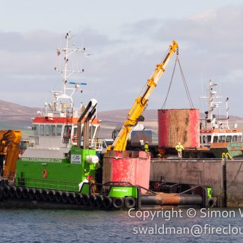 """Green Isle"" workboat lifting sections of Pelamis"