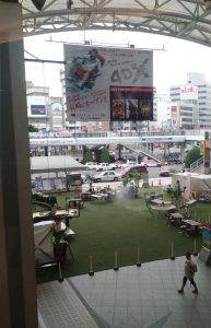 An area of fake grass with food stalls and chairs/tables on it, between a railway station and a busy road & bus station