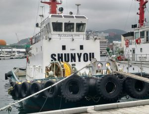 """Tug boat with its name """"SHUNYOU"""" painted in large capitals on the front of the superstructure."""