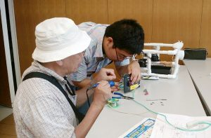 Japanese teacher helping Japanese school student with soldering.