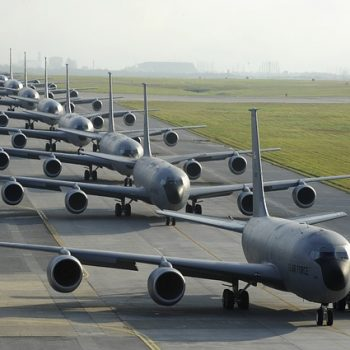 A slightly surreal row of grey aircraft lined up on a runway