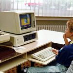 Young person looking at an early IBM PC-compatible.