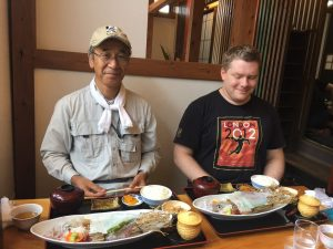 Me and a Japanese professor, each with a plate of transparent squid sashimi in front of us