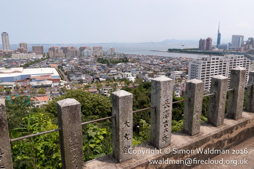 Foreground: inscribed stone fenceposts of a temple; mid-ground: cityscape; background: sea.