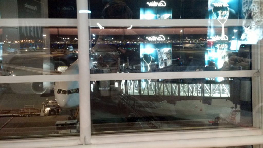 View through a window - Cartier store reflected in the glass, and planes behind.