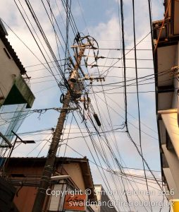 A mess of overhead power cables meeting at a street junction