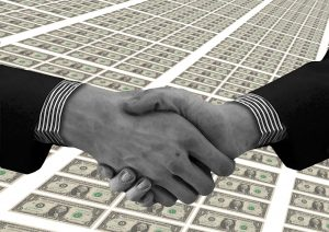 Two men in suits shaking hands across a large amount of money