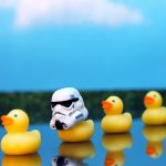 A row of yellow plastic ducks, where the second one is wearing a stormtrooper helmet from Star Wars