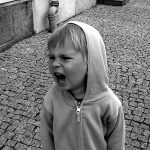 Small child in a hoodie shouting.