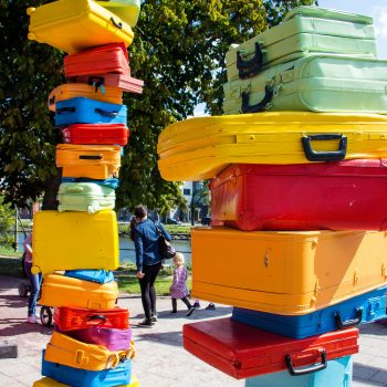 Photograph of an art installation consisting of two very high piles of brightly coloured luggage.