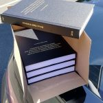 Four copies of a hard-bound thesis, posed in a box in the sun.