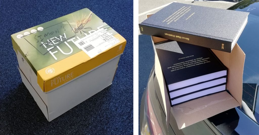 "Two pictures. On the left, a cardboard box with ""Simon's Thesis"" scrawled on the top in marker. On the right, four hard bound theses - black books with gold lettering."